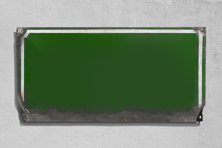 Rusty green metallic sign with rough wall background.
