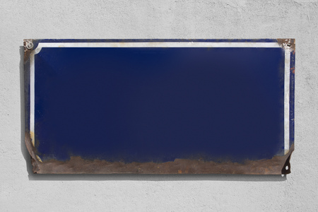 Rusty blue metallic sign with rough wall background. Imagens