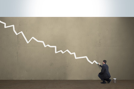 A business man draws a falling chart on a concrete barrier.