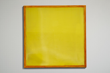 Yellow screen printing frame used as sign with grey background.