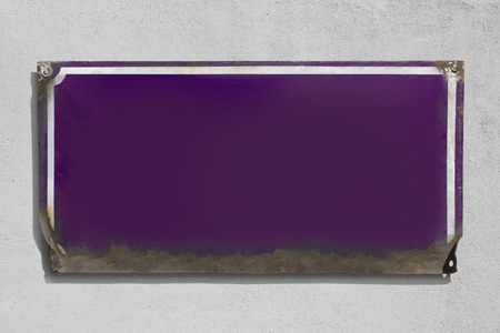 Rusty violet metallic sign with rough wall background.