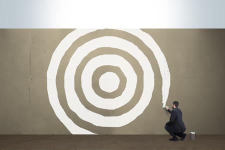 A business man draws a target on a concrete barrier. Imagens