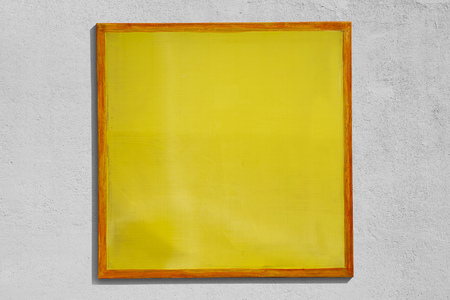 Yellow screen printing frame used as sign with rough wall background.