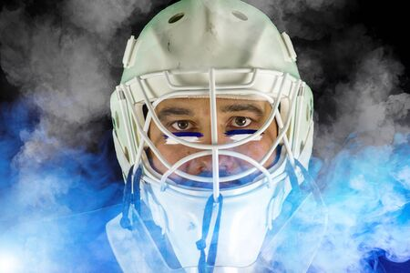 This is a detail hockey goalie. He is concentrated on the game. He has blue and white smoke around his face. Zdjęcie Seryjne