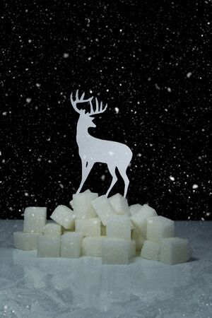 Paper deer, white sugar cubes, ice surface, darkness and snow in one photo.