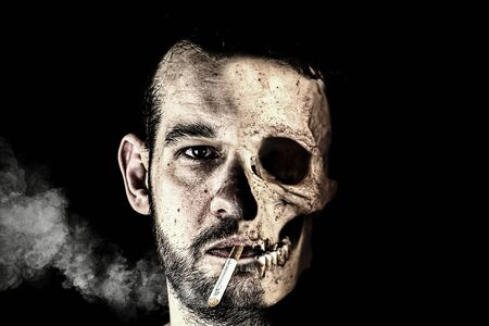 Half male face and half skull. There is a burning cigarette in his mouth, from which smoke comes. Double face. Stockfoto