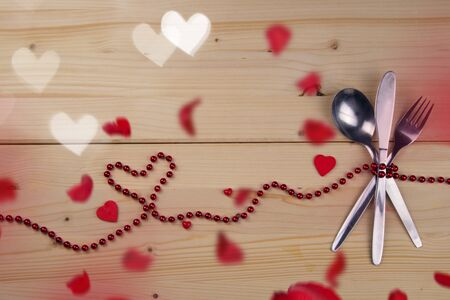 Valentine concept. Fork, knife and tablespoon tied with red pearls. Hearts and petals bokeh.Invitation to the Valentine`s menu. Spoon, fork, knife, red pearls, hearts and petals.