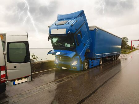 A broken truck, with the cab lowered, is waiting for a repair car service.It`s storm and lightning.Broken truck, mobile car service, highway and storm. Traffic complications.
