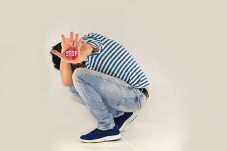 MAN ME TOO. The man covers his head, curls up and has his hand outstretched, with a stop sign on his palm.Man in defensive position, showing gesture stop. Curled Person on White Background.