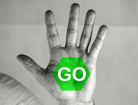 Man holds palm in front of him. He has an inscription and a GO sign on his palm. Black and white photo with green sign. Friendly gesture.