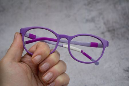 Woman holding old, broken children`s glasses without lens.Broken children`s glasses. The glasses don't have lens and they are scratched.