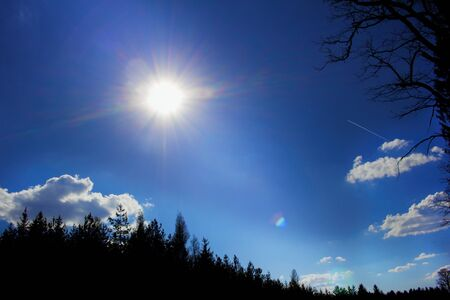 Sun burst. The afternoon sun is burning. Blue sky and a few white clouds.Sun and sunbeams in the azure sky and diffraction glow. Stock Photo