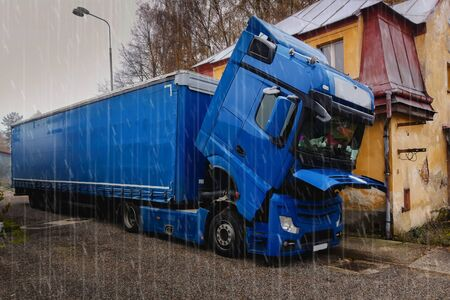 A broken truck, with the cab lowered, is waiting for a repair car service.It`s rainy.Broken truck next to the old house. Traffic complications.