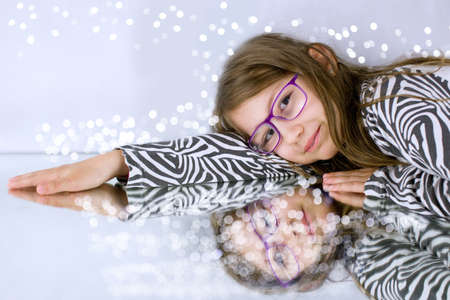 Little girl with  glasses and her reflection under small spotlights.