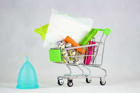 Blue menstrual cup and sanitary napkins and tampons in shopping cart.Menstrual cup - a modern aid during menstruation for a modern woman versus sanitary napkins and tampons.