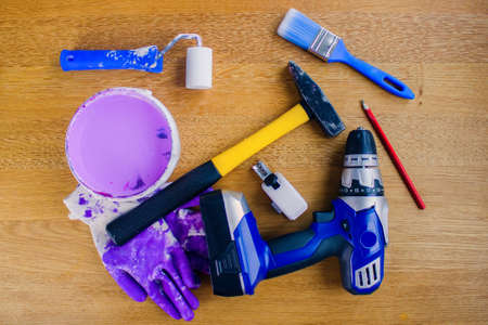Reconstruction can begin. Concept with hand tools.Cordless drill, tape measure, pencil, roller, lilac paint, brush, hammer and dirty work gloves.
