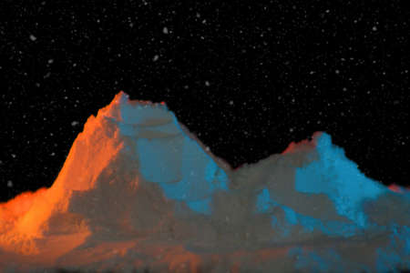 Snowy mountains in colored light and aurora borealis.Two mountain peaks covered with snow duvet. Orange and blue light falls on the mountains.