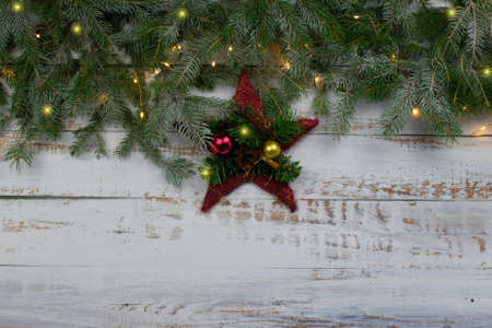 Coniferous spruce branches  with snow and  decoration on white abraded boards. Natural Christmas and winter background or concept.