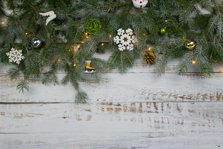 Coniferous spruce branches  with snow and LIGHT CHAIN white abraded boards. Natural Christmas and winter background or concept.