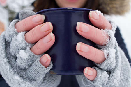 Woman holding a mug in her hands. The gloves are covered in snow. It`s freezing.Front view of frozen hands of a young woman holding a mug.