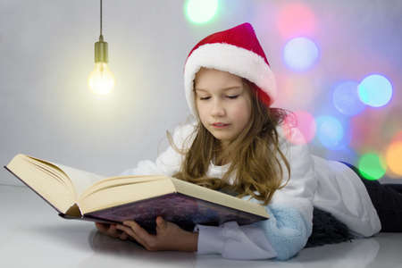 Little girl in a Christmas hat of Santa Claus reads in a book. Colour Lights are shining all around.