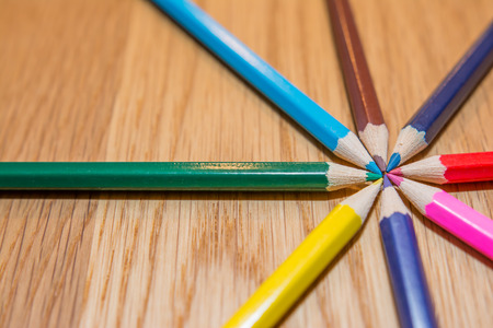 Color pencils in circle on wooden table photo