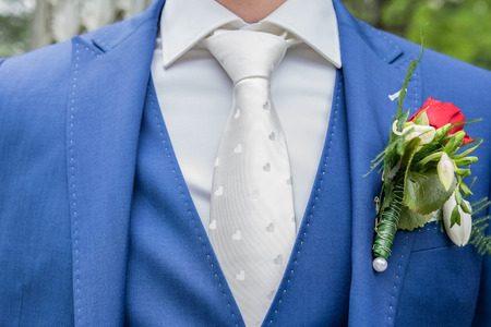 Groom with blue suit and white tie photo