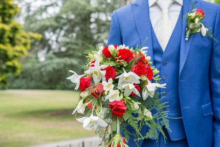 Bräutigam hält Hochzeitsstrauß mit blauen Anzug und weißer Krawatte Standard-Bild