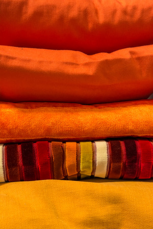 domestication: Yellow and orange colored pillows stacked on top of each other