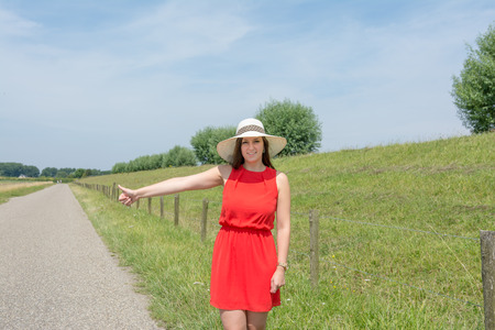 woman wearing hat: Woman wearing hat and red dress, hitchhiking on roadside