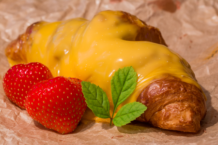 Croissant topped with melted cheese, with strawberrys and mint