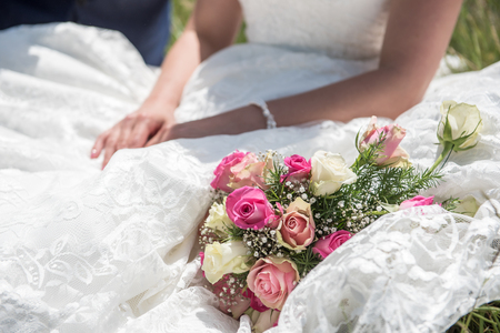 Bride sitting down with bouquet on her dress