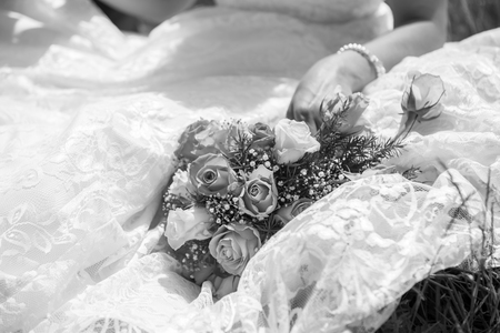 Bride sitting down with bouquet on her dress in black and white Stock fotó