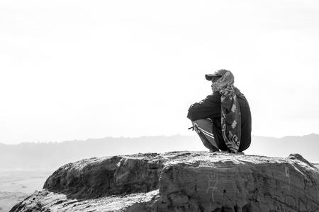 Indonesian local horseman sitting on a rock Stock fotó