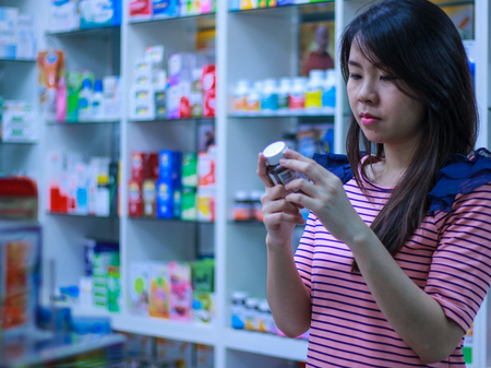 A woman is reading retail of drug for information before buy this product 版權商用圖片