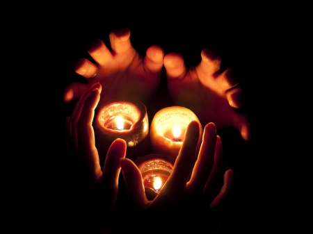 Burning candles and hands in darkness photo