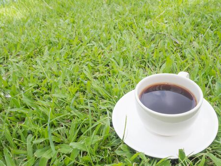 The shadow of the sky in  black coffee with white cup on the grass. Reklamní fotografie