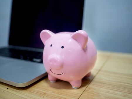 Pink piggy bank standing in front of laptop on wooden floor. step up start up business to success, Saving money for future plan and retirement fund concept.