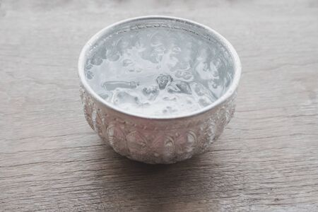 Ice water in the Thai silver bowl is placed on the plank, Beautiful Thai tradition hospitality. Zdjęcie Seryjne