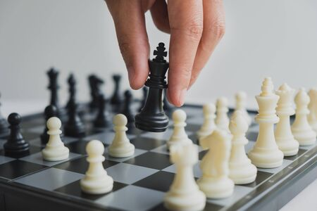 hand holding chess pieces on board with white background, driven to success Business Strategy.
