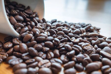 Coffee beans are spilling from the cup,  ready to give freshness and alongside the businessmen. Reklamní fotografie
