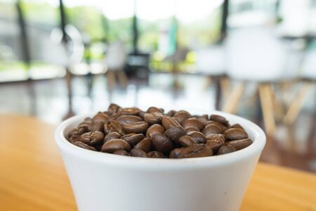 Coffee beans  from the cup, ready to give freshness and alongside the businessmen. Reklamní fotografie