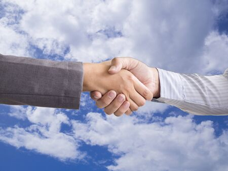 Hand shake in front of blue sky, business dual with new goal and success concept. Foto de archivo - 129896196