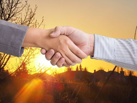 Hand shake in front of morning sun rise, business dual with new goal and success concept. Foto de archivo - 129896199