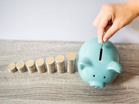Woman hand putting coin into blue piggy bank with coins pile growth graph, saving money for future investment plan and retirement fund concept.