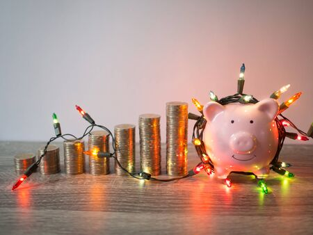 Pink piggy bank with coins pile growth graph and Party lights, Funly saving money for future investment plan and retirement fund concept.