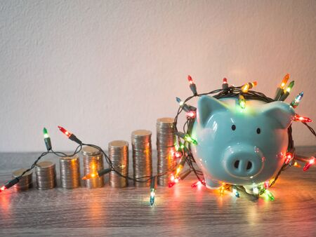 Blue piggy bank with coins pile growth graph and Party lights, Funly saving money for future investment plan and retirement fund concept. Reklamní fotografie