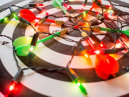 Target six dart focus on bulls eye Dart Board with party light, Funly setting challenging business goals And ready to achieve the goal concept.