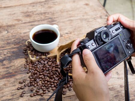 The photographer is intending to use digital camera take pictures a cup of blak coffee and coffee beans.