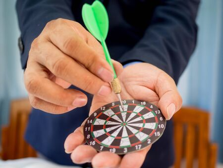 Businessman holding a darts aiming at the target center of dart board, Setting challenging business goals And ready to achieve the goal concept. Stock Photo